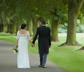 Newly wed couple walking in park