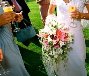 Mid section of bride at wedding holding glass and bouquet